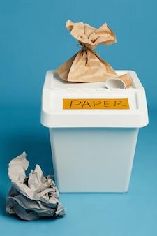 Vista a tutta lunghezza al bidone della spazzatura etichettato per i rifiuti di carta, lo smistamento e il concetto di riciclaggio