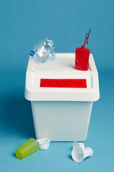 Vista a tutta lunghezza al bidone della spazzatura etichettato per i rifiuti di plastica, lo smistamento e il concetto di riciclaggio