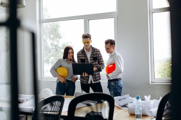 Vista a tutta lunghezza del team di giovani architetti professionisti che lavorano in ufficio, uno dei quali tiene in mano un laptop. concetto di costruttori