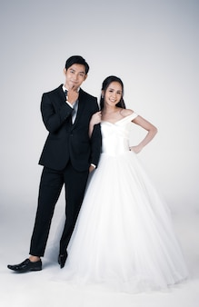 Integrale di giovane coppia asiatica attraente, presto per essere sposa e sposo, donna che indossa abito da sposa bianco. uomo che indossa uno smoking nero, in piedi insieme. concetto per la fotografia prematrimoniale.