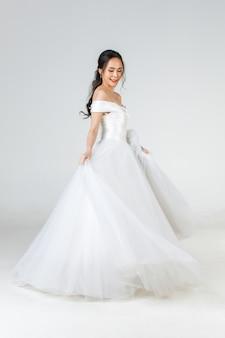 Tutta la lunghezza di una giovane donna asiatica attraente, che presto sarà sposa, con indosso un abito da sposa bianco che sembra felice di girare. concetto per la fotografia prematrimoniale.