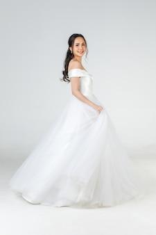 Tutta la lunghezza di una giovane donna asiatica attraente, prossima sposa, che indossa un abito da sposa bianco che sembra felice di girare concetto per la fotografia prematrimoniale.