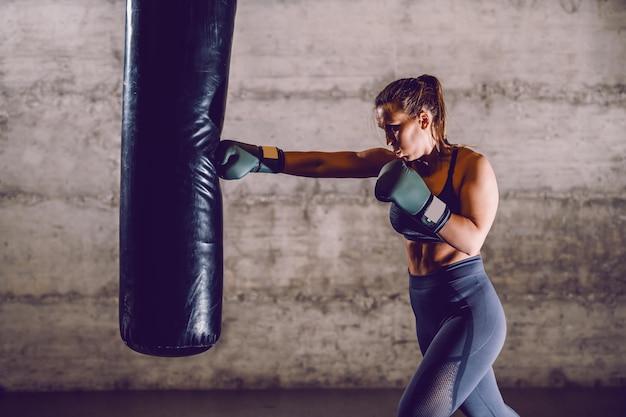 Integrale di giovane pugile femminile muscolare caucasico dedicato in abiti sportivi