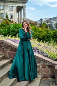 Giovane donna elegante integrale in bello gress verde che sta nella scala di pietra, stile di vita della città