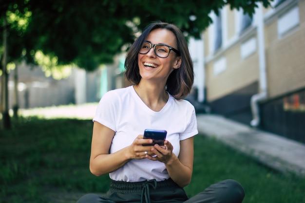 Figura intera di una giovane ragazza, con gli occhiali sul viso, con un telefono in mano, sorridente, che si diverte fuori.