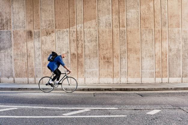 Lunghezza completa di un giovane in bicicletta in città