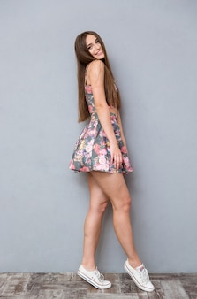 Per tutta la lunghezza di una giovane donna affascinante allegra piuttosto felice in top floreale estivo e gonna con capelli lunghi in posa su un muro grigio