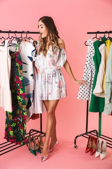 Integrale di giovane donna in abito in piedi vicino al guardaroba con vestiti e scegliendo cosa indossare isolato sul rosa