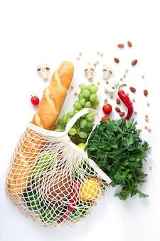 Borsa a rete piena di diversi alimenti naturali su sfondo bianco. flatlay vista dall'alto