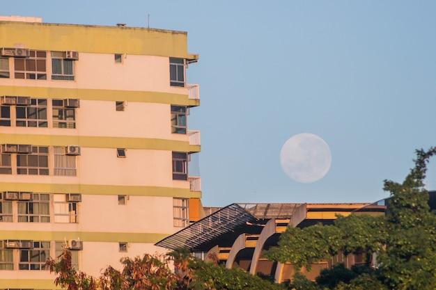 Luna piena su un edificio sulla spiaggia di botafogo a rio de janeiro, brasile.