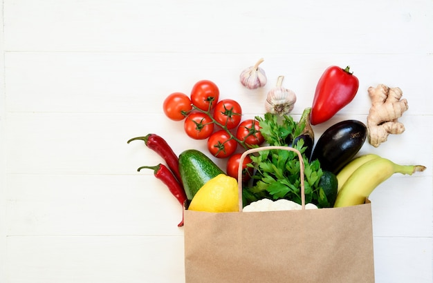 Sacchetto di carta pieno di cibo sano su uno sfondo bianco. eco shopping e concetto di consegna del cibo. concetto di rifiuti zero.