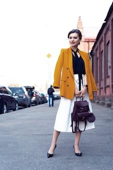 Foto completa di una giovane donna d'affari felice ed elegante che cammina per strada
