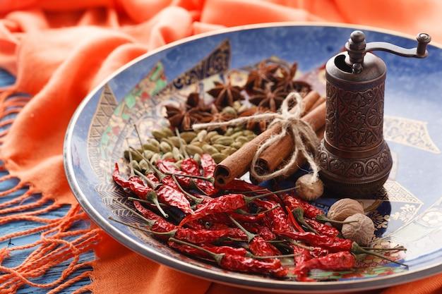 Zolla piena delle spezie asiatiche con i peperoncini rossi sulla tabella blu