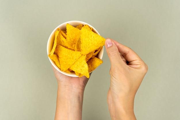 Un piatto pieno di triangoli di mais nachos croccanti nelle mani delle donne.