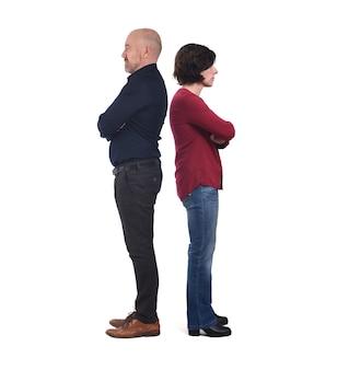 Ritratto completo di una coppia schiena contro schiena su bianco, braccia incrociate