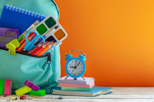 Zaino scuola completa con diverse forniture su arancio. il concetto torna a scuola.