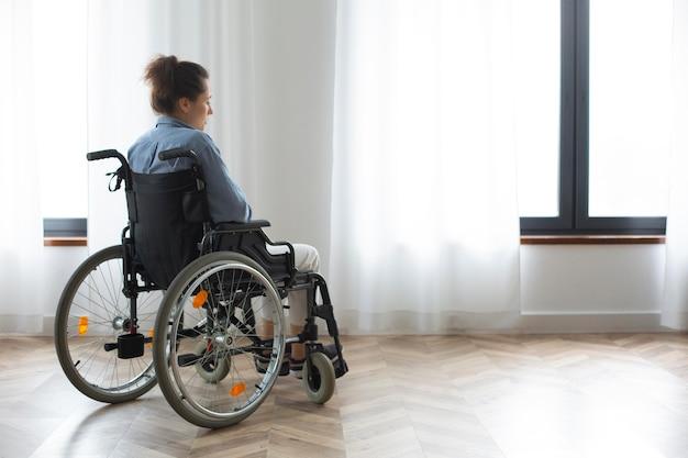 Colpo intero donna sola in sedia a rotelle