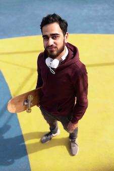 Ragazzo pieno di colpi con cuffie e skateboard