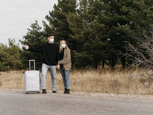 Coppia full shot autostop con i bagagli