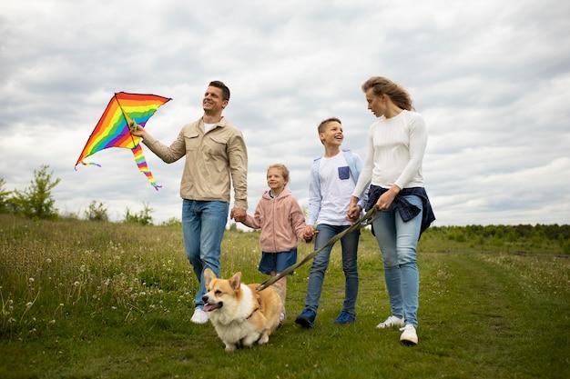 Famiglia a tutto campo con aquilone e cane carino