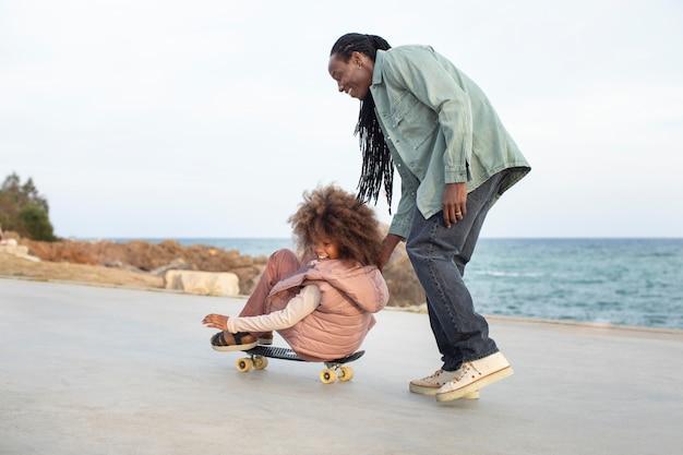 Padre e ragazza a tutto campo con penny board