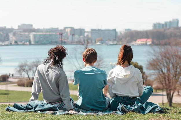 Amici del colpo pieno che si siedono sull'erba