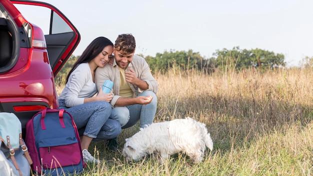 Coppie felici del colpo pieno che esaminano cane