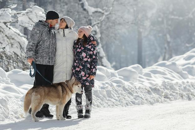 Full shot famiglia felice con il simpatico cane