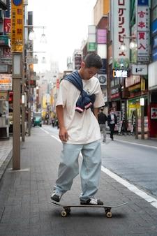 Uomo giapponese a tutto campo con lo skateboard