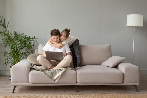 Bambino pieno del colpo che abbraccia genitore sul divano
