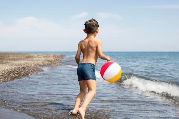 Ragazzo a tutto campo che gioca con la palla in spiaggia