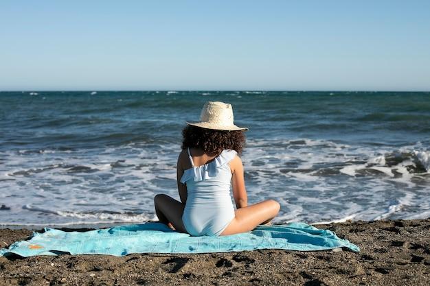 Ragazzo a tutto campo seduto sulla spiaggia