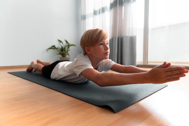 Ragazzo a tutto campo sul tappetino da yoga