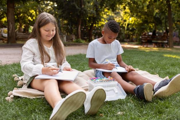 Bambini a tutto campo che disegnano insieme