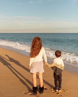 Bambini del colpo pieno che tengono le mani alla spiaggia
