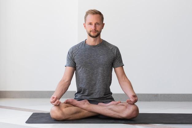 Uomo pieno del colpo che fa yoga all'interno