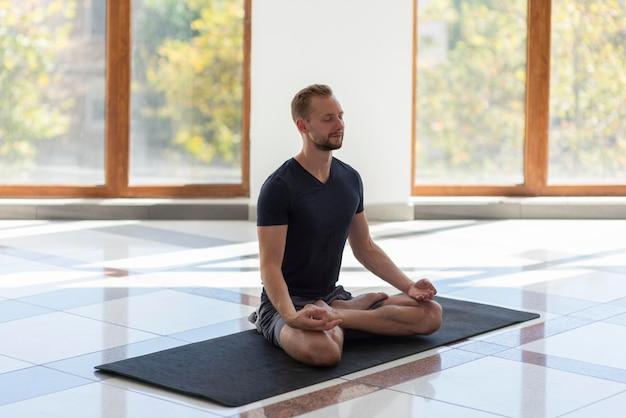 Uomo pieno del colpo che fa yoga sulla stuoia
