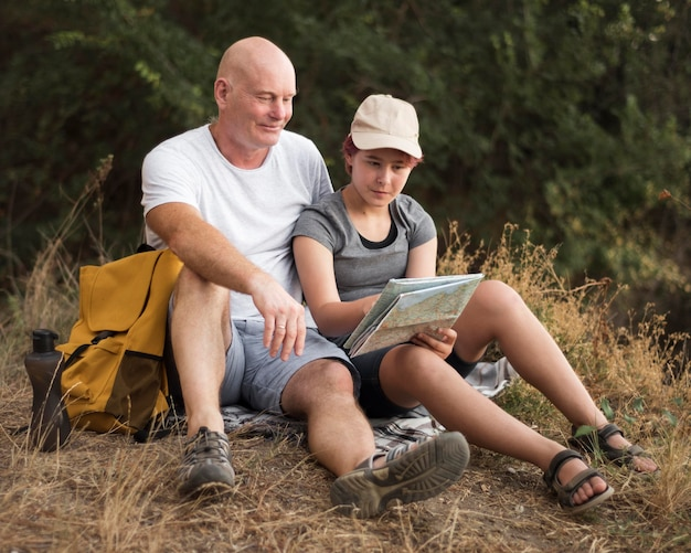 Uomo e ragazza del colpo pieno che si siedono sull'erba Foto Premium