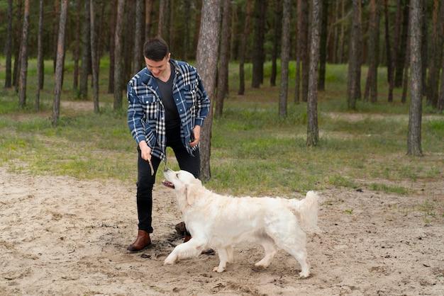Uomo a tutto campo che gioca con il cane