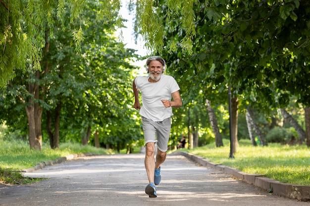 Uomo della foto a figura intera che corre nel parco