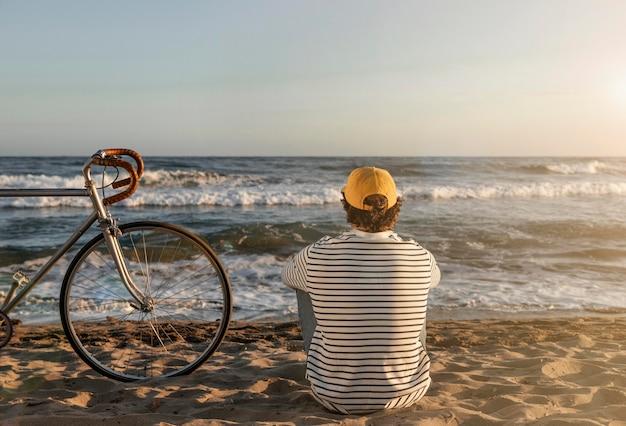 Uomo pieno del colpo che si siede sulla spiaggia