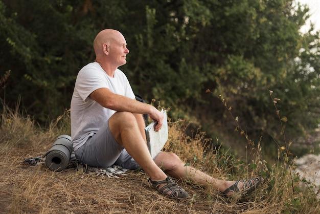 Uomo pieno del colpo che si siede sull'erba Foto Premium