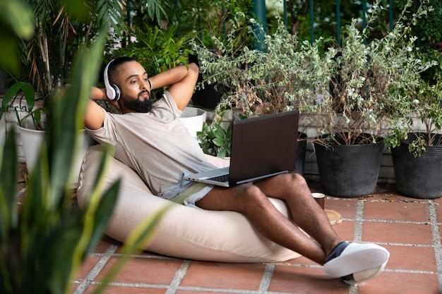 Telelavoro completo dell'uomo del colpo con il computer portatile