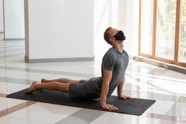 Uomo completo del colpo che indossa la maschera e che fa yoga al coperto