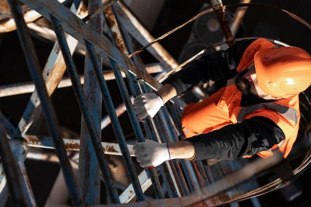 Uomo pieno del colpo con la scala rampicante dell'attrezzatura