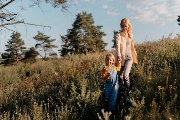 Madre e ragazza a tutto campo che si tengono per mano