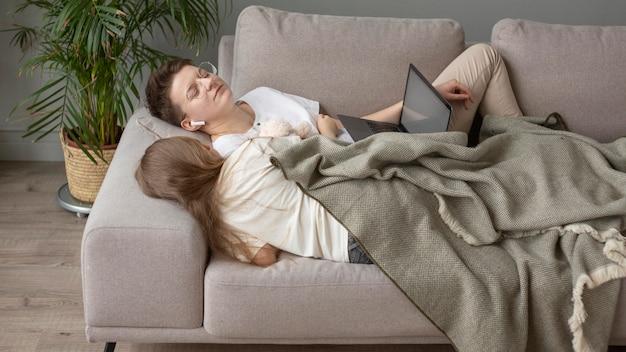 Full shot genitore e bambino che dorme sul divano