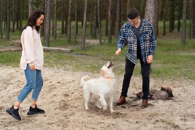 Persone a tutto campo che giocano con il cane