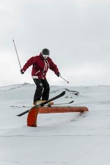 Sciatore del colpo pieno con attrezzatura che salta