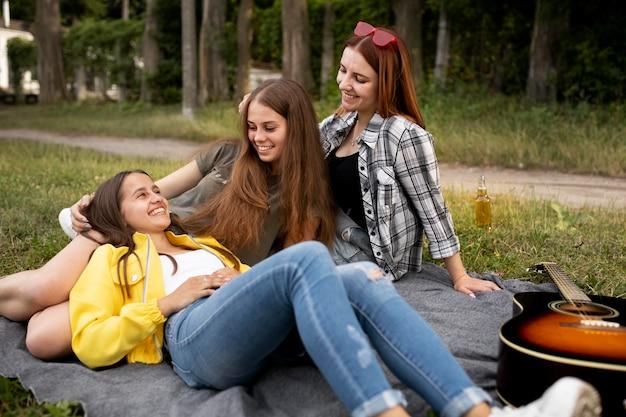 Amici sorridenti a tutto campo con la chitarra